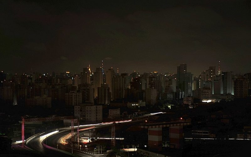 Residential buildings in the Moema neighborhood stand in darkness, the city lit solely by antennas atop buildings and vehicles headlights, during a massive blackout in Sao Paulo, Brazil, early November 11, 2009. A massive blackout across the southern half of Brazil has plunged tens of millions of people into darkness and prompted a major police mobilization amid fears of an opportunistic crime wave. AFP PHOTO/Mauricio LIMA (Photo by MAURICIO LIMA / AFP)