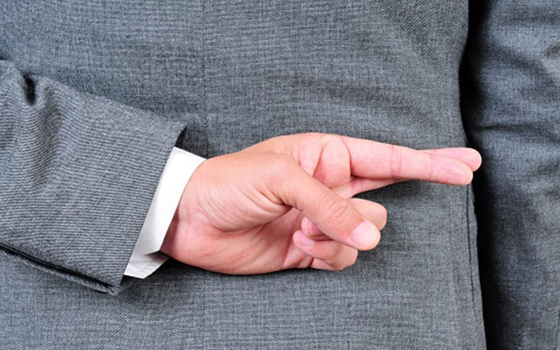 a man wearing a suit crossing his fingers in his back