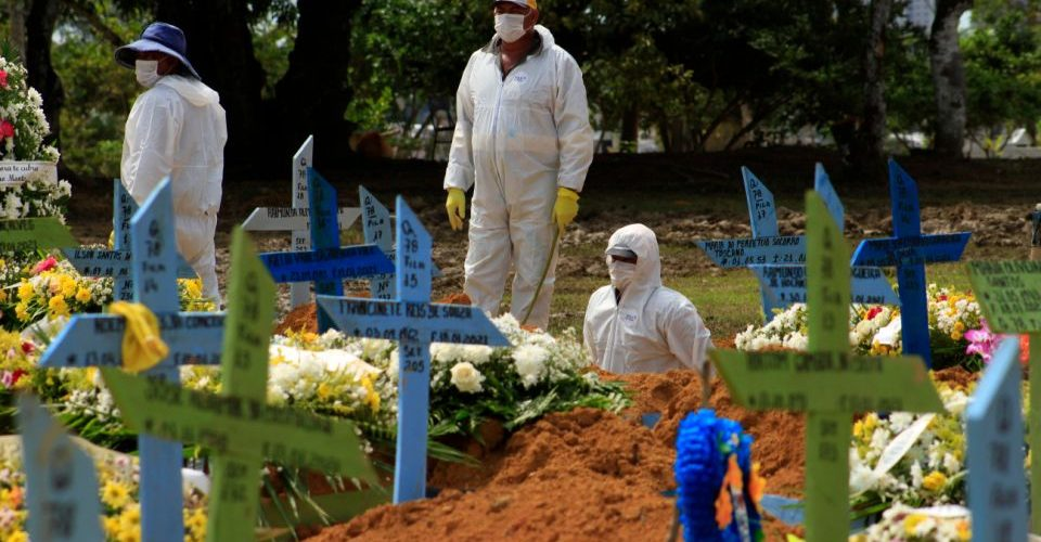 Gravediggers are seen during a funeral of a COVID-19 victim at the Nossa Senhora Aparecida cemetery in Manaus, Amazonas state, Brazil, on January 22, 2021, amid the novel coronavirus pandemic. (Photo by MARCIO JAMES / AFP) (Photo by MARCIO JAMES/AFP via Getty Images)