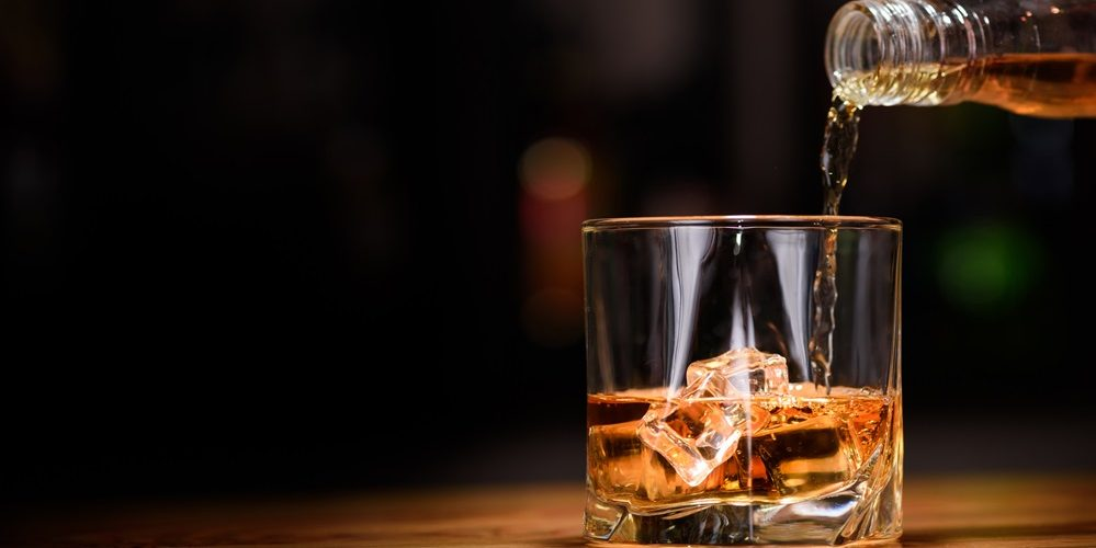 Still life. pour or whiskey in to glass.